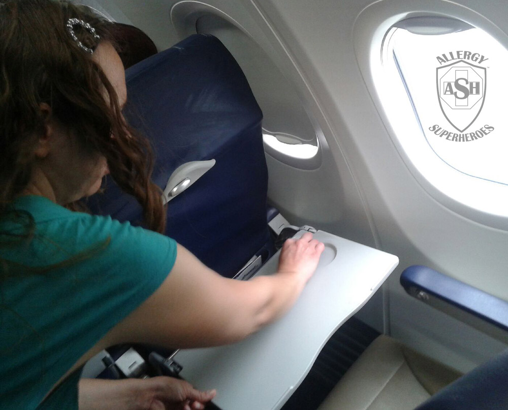 Wiping down an airplane tray table before taking a flight | Allergy Superheroes