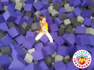 Kal having fun with foam blocks at a food allergy inclusive birthday party by Allergy Superheroes.