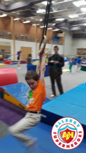 Kal swinging on the rings at a food allergy inclusive birthday party by Allergy Superheroes.