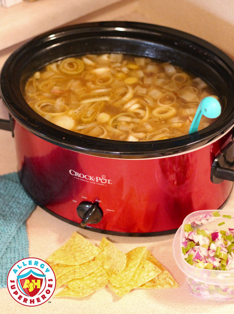 CrockPot of soup with tortilla chips and onion garnish ready to be used | by Food Allergy Superheroes