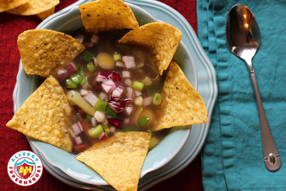 Bowl of soup with tortilla chips and onion garnish from above | by Food Allergy Superheroes