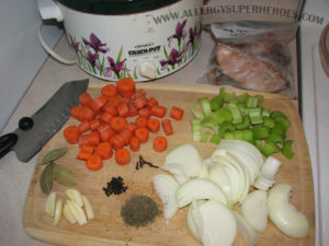 Chopped carrots, celery, onions, garlic, and herbs in front of crockpot | by Food Allergy Superheroes