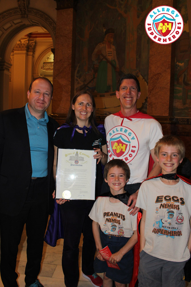The Allergy Superheroes Family with Governor Jared Polis, holding the Food Allergy Week Proclamation | by Food Allergy Superheroes