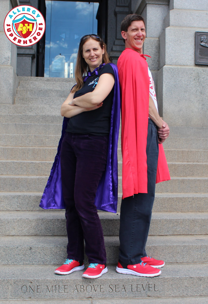 Eileen and Dean of Allergy Superheroes stand back-to-back outside the Colorado State Capitol in red sneakers, Allergy Superheroes shirts, and capes | by Food Allergy Superheroes