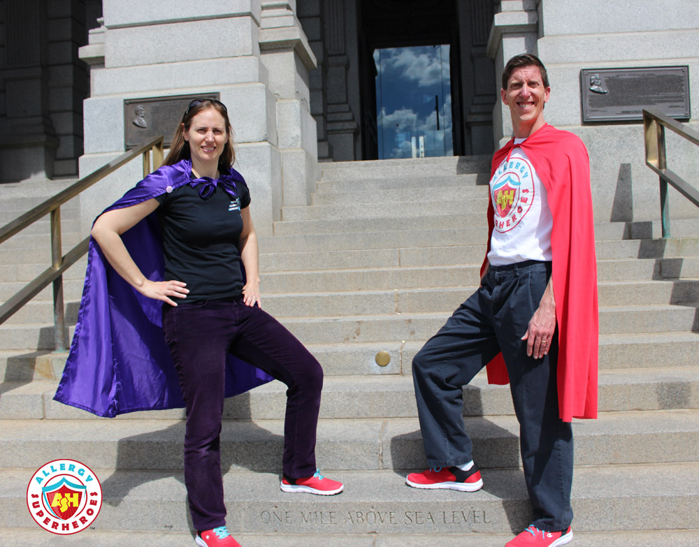 Eileen and Dean of Allergy Superheroes stand outside the Colorado State Capitol in red sneakers, Allergy Superheroes shirts, and capes | by Food Allergy Superheroes