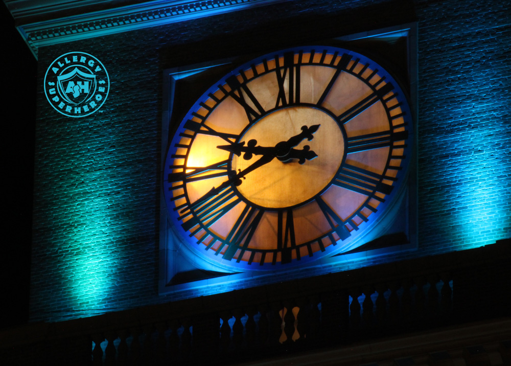 The clock face of Denver's D&F Clock Tower on 16th Street Mall, with the top floors lit up Teal for Food Allergy Awareness | by Food Allergy Superheroes