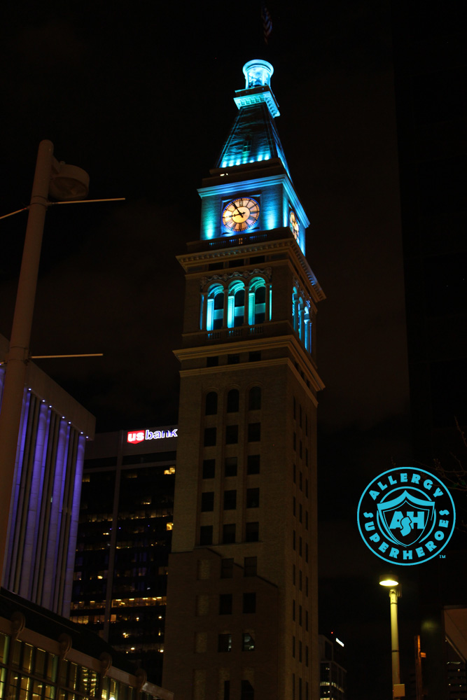 Denver's D&F Clock Tower on 16th Street Mall tall shot, with the top floors lit up Teal for Food Allergy Awareness | by Food Allergy Superheroes