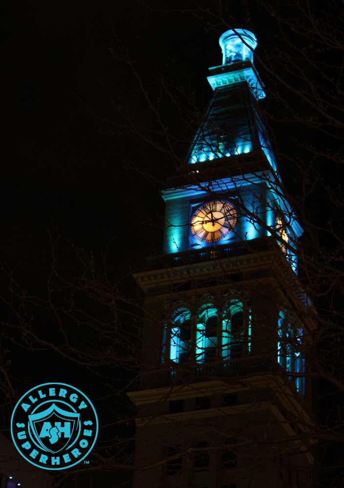 Denver's D&F Clock Tower on 16th Street Mall, with the top floors lit up Teal for Food Allergy Awareness, viewed dramatically through the branches of a tree | by Food Allergy Superheroes