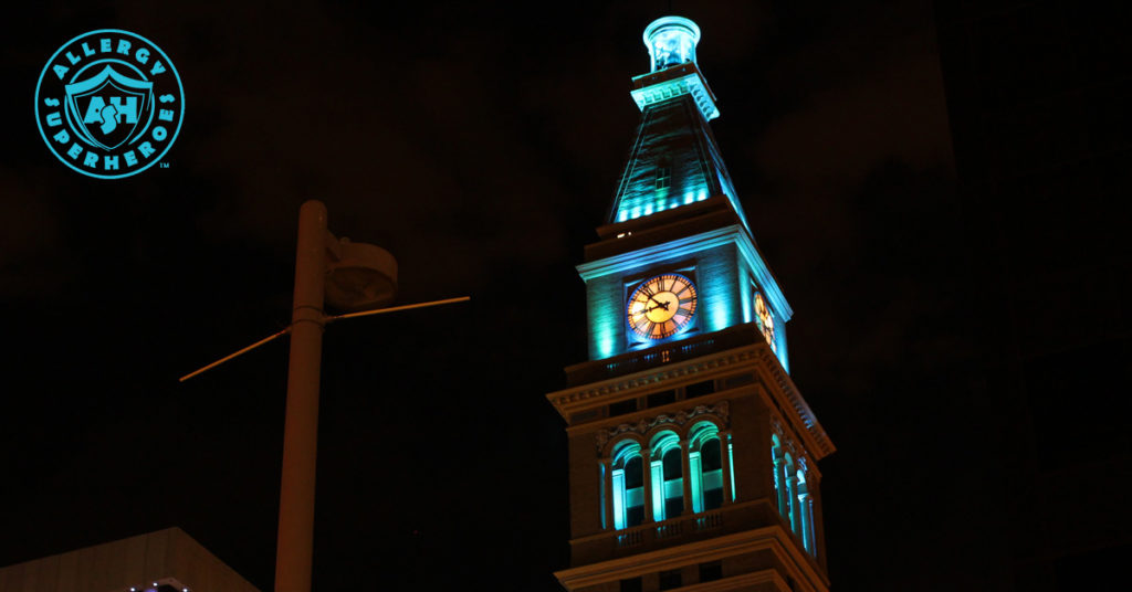 Denver's D&F Clock Tower on 16th Street Mall wide shot, with the top floors lit up Teal for Food Allergy Awareness | by Food Allergy Superheroes