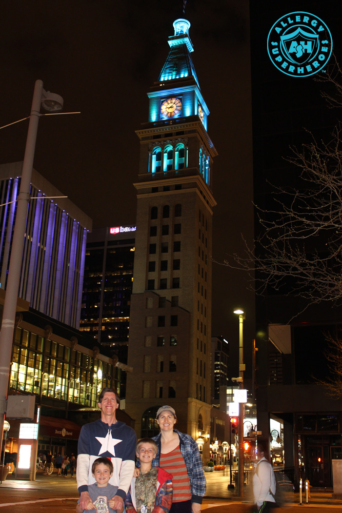 Denver's D&F Clock Tower on 16th Street Mall, with the top floors lit up Teal for Food Allergy Awareness, with the Allergy Superheroes Family standing in front of it | by Food Allergy Superheroes