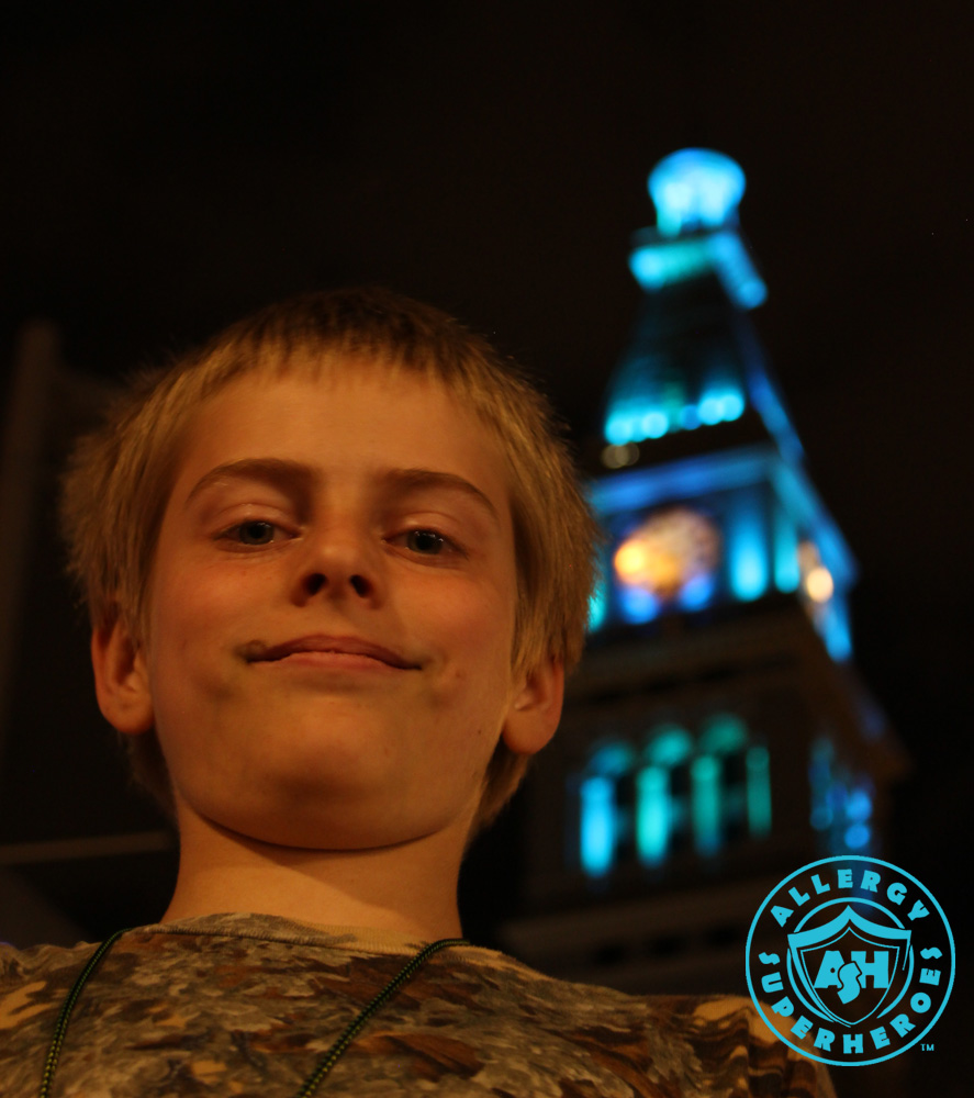 Denver's D&F Clock Tower on 16th Street Mall, with the top floors lit up Teal for Food Allergy Awareness, with a child standing in the foreground | by Food Allergy Superheroes